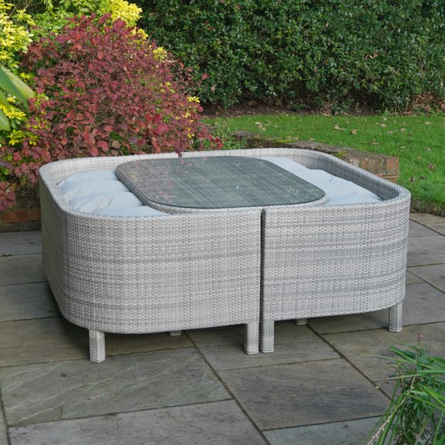 A luxury outdoor rattan sofa suite comprising 2 3 seater sofas and a dining table, in closed configuration with the sofas close up to the table