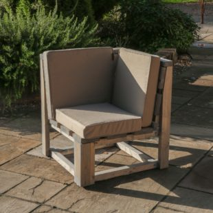 An outdoor wooden individual corner seat with cushions that is part of the Warwick Modular sofa set.