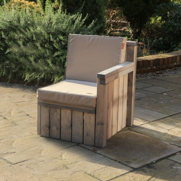 An individual outdoor wooden sofa seat with cushion and armrest that makes up the warwick modular sofa with other seat components joined to it. located on a patio