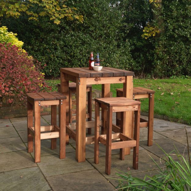A square wooden poseur bar table with 4 wooden bar stools arranged around it located on a patio