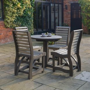 An outdoor round dining table and four chairs made from 100% recycled plastic located on a patio
