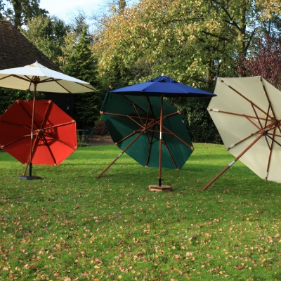 A group of large outdoor parasols in cream, blue, red and green open and displayed on a lawn