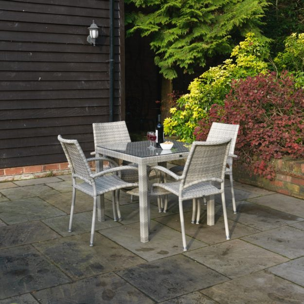 A square rattan dining table with glass table top and 4 arm chairs arranged around it located on a patio