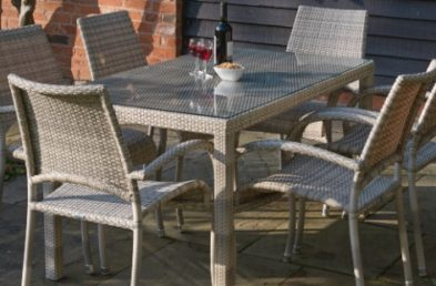 A cream grey rattan dining table and chairs set on a patio
