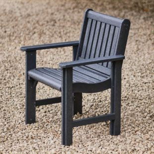 A dark grey recycled plastic carver chair on a gravel patio