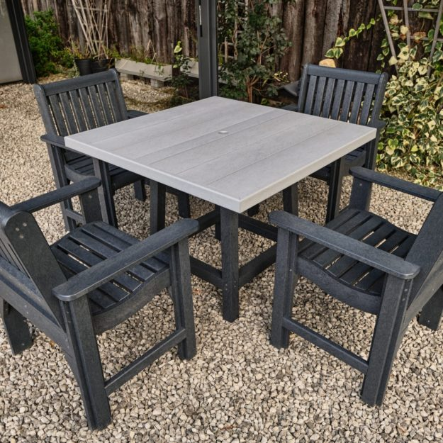 A square outdoor table made from 100% recycled plastic in 2 tone grey with 4 dark grey recycled plastic carver chairs around it on a gravel patio