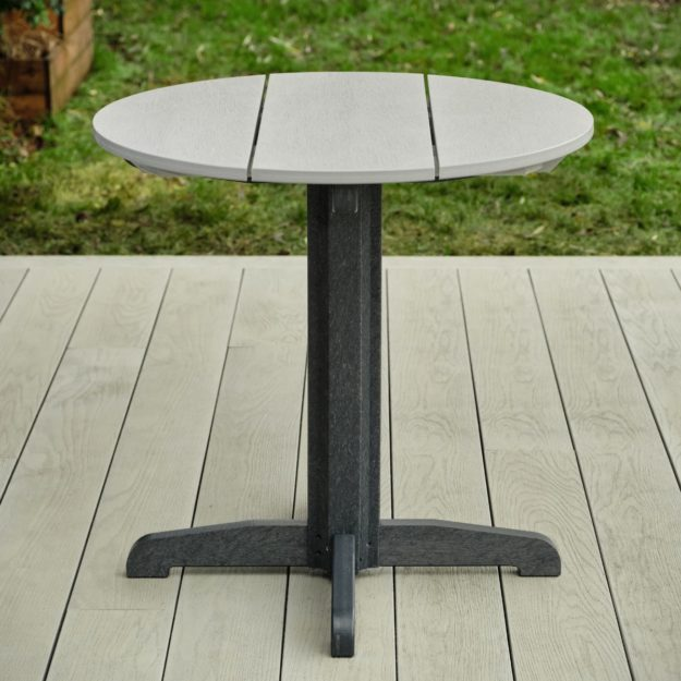 A two tone grey round outdoor dining table with a pedestal base made entirely from recycled plastic on a grey deck