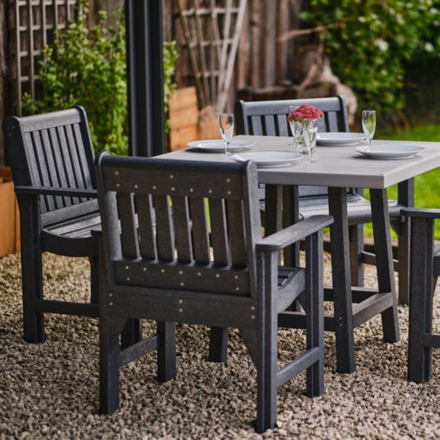 A square recycled plastic outdoor dining table and dining arm chairs on a gravel patio