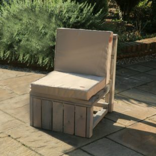 A luxury outdoor square cushion for back and seat in bedrock grey colour on a wooden sofa seat located on a patio