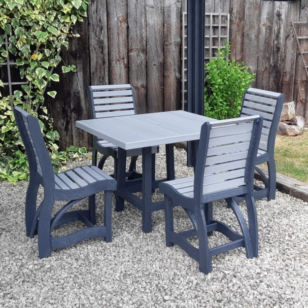 A square outdoor dining table made from recycled plastic with 4 chairs around it in grey on a gravel surface