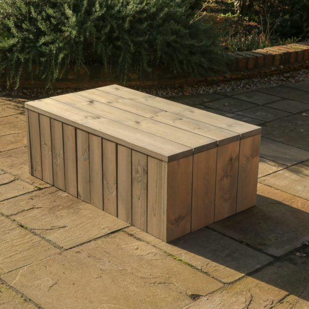 A rectangular wooden coffee table with internal cushion storage for outdoor use, located on a patio