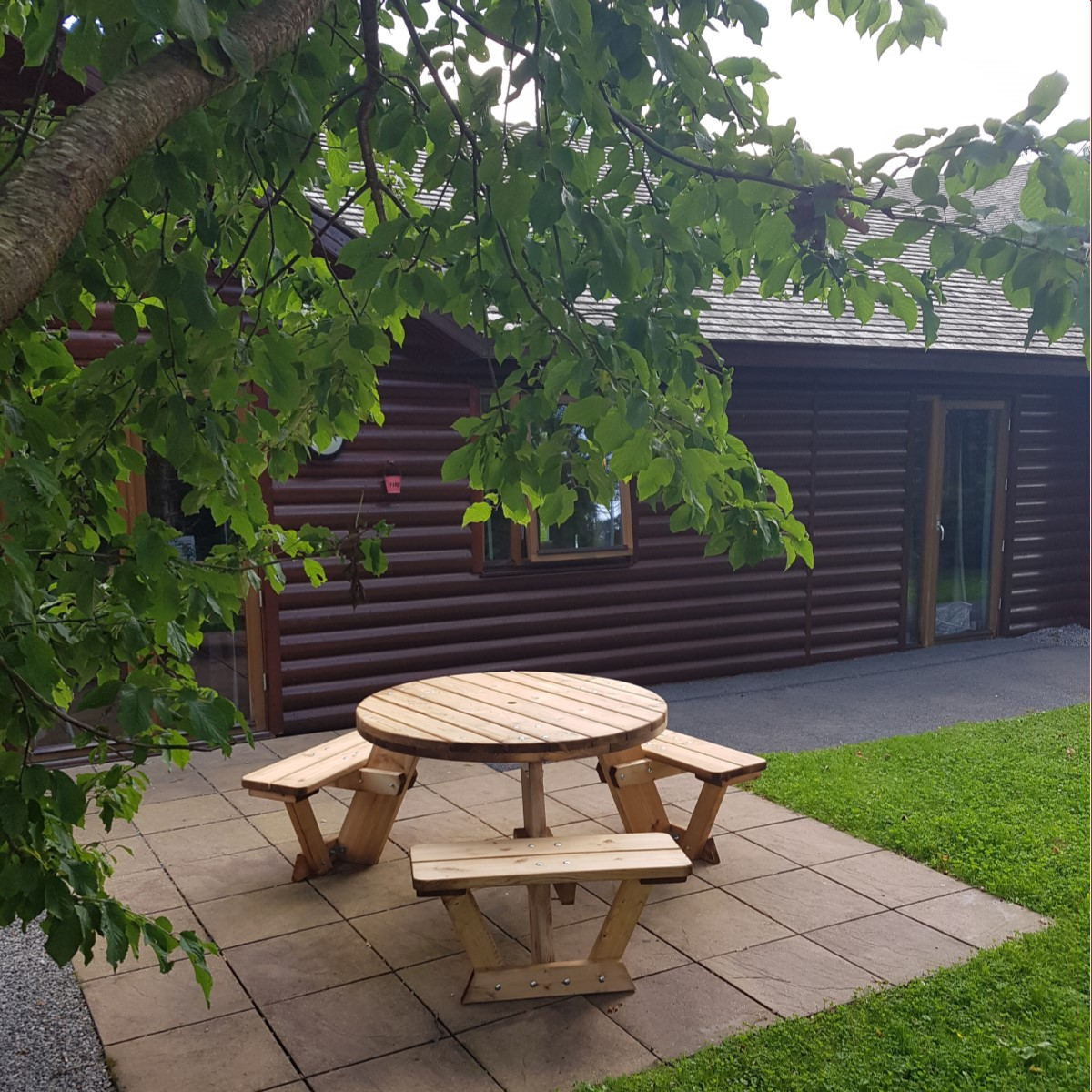 A circular wooden picnic table to seat 6 people on a patio at a holiday park