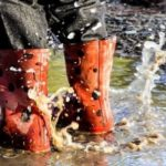 the welly clad feet of a child splashing in a muddy puddle