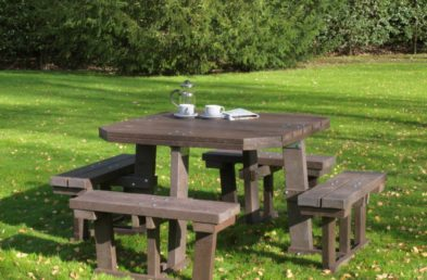 A large well made square 8 seater picnic table made from recycled plastic in a garden setting