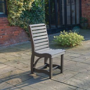 A sleek looking recycled plastic outdoor dining chair in two tone of grey located on a patio
