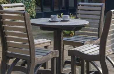 An outdoor dining table and 4 chairs made from 100% recycled plastic located on a pub patio