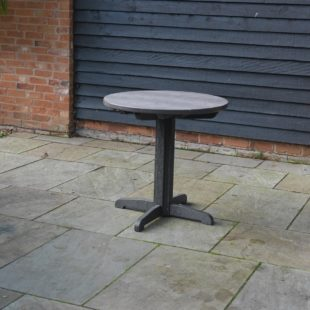 A sleek grey round outdoor dining table made from smooth recycled plastic on a patio