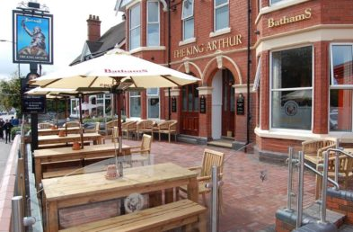 The front of a pub with outdoor tables, benches and parasols