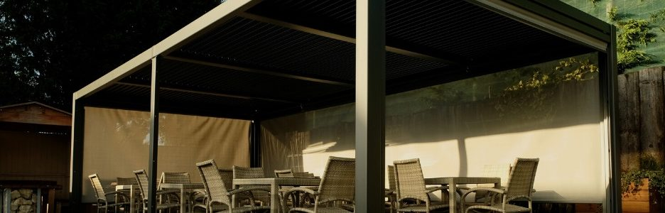 A luxury rectangular metal gazebo 3.5m wide x 7.2m long with rattan dining tables and chairs underneath it