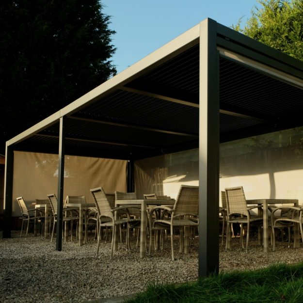 A large rectangular luxury metal gazebo with side blinds inside there are 6 4 seater cream grey rattan tables and 24 chairs
