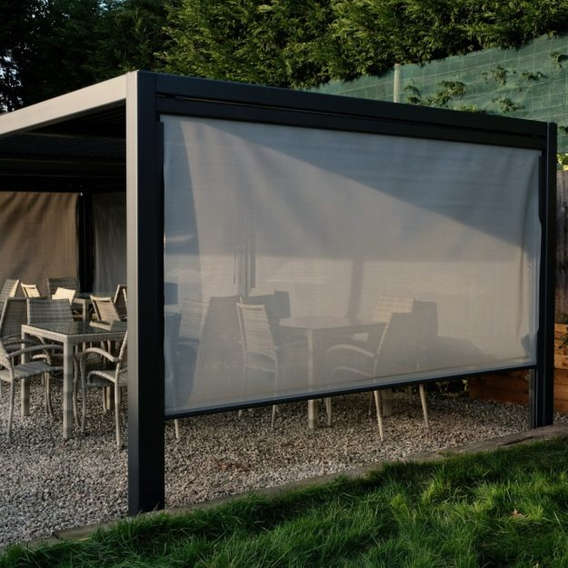 A luxury rectangular grey metal gazebo with rattan dining funiture underneath and a side blind down