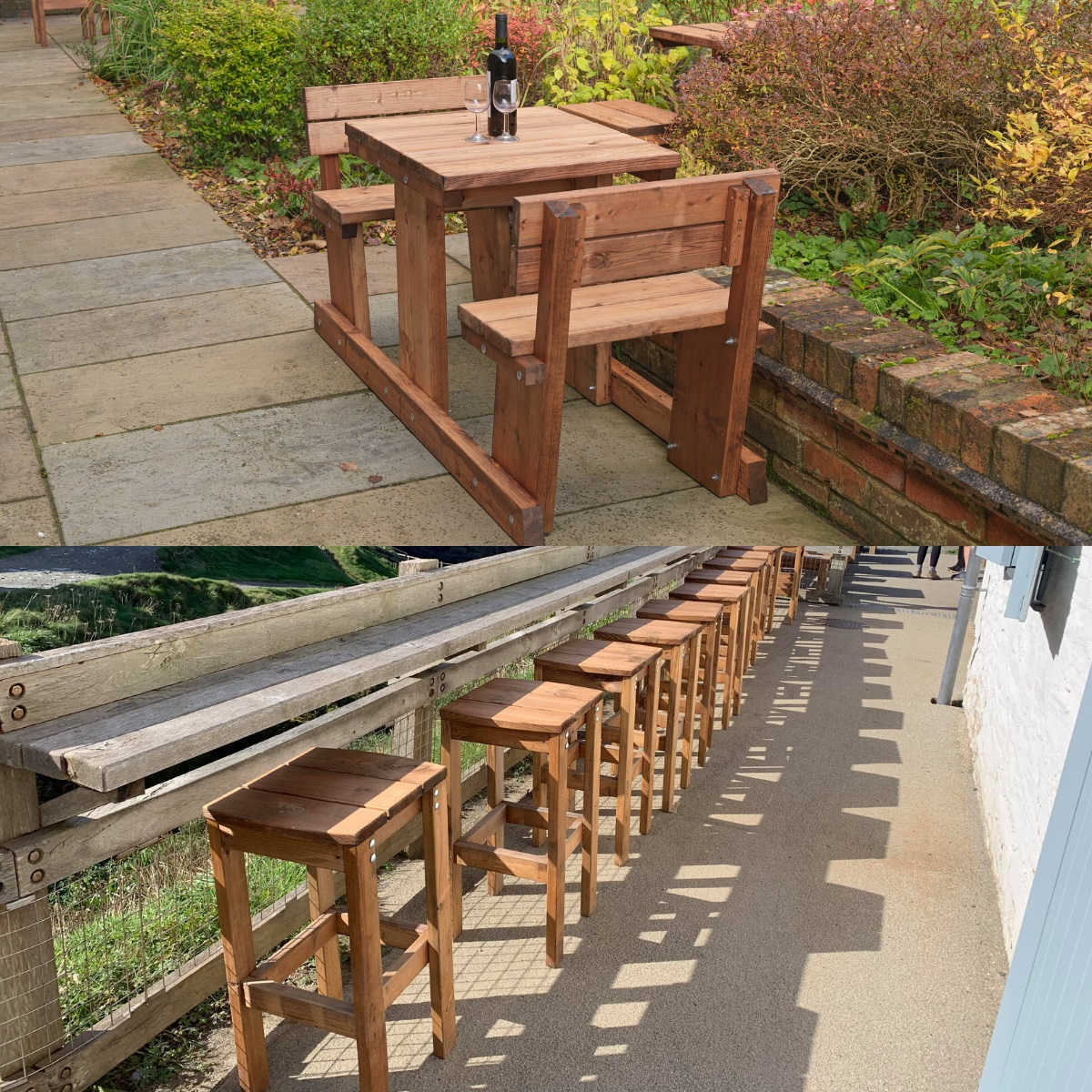 A 2 seater wooden picnic table at the edge of a pub patio and a line of bar stools against a fence which has a shelf at tintagel castle cafe