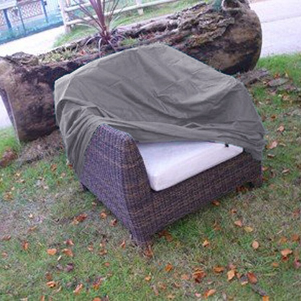A UPVC weather cover half covering a rattan armchair located on grass