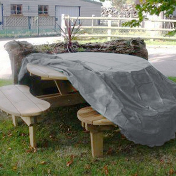 A UPVC weather cover half covering a circular wooden picnic table located on grass