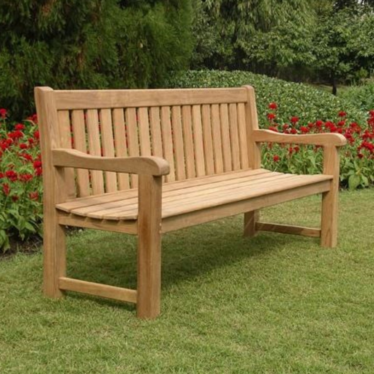 A 1.8m teak park bench with thick slats at the back and seat located on a lawn with a bright flower bed behind it