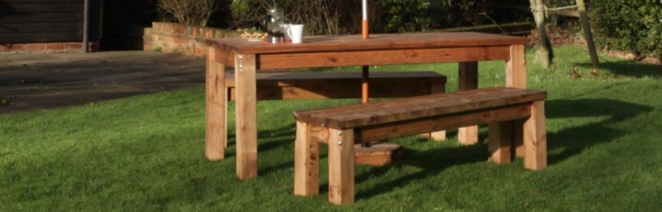 A rectangular wooden outdoor table and two matching benches on a pub lawn