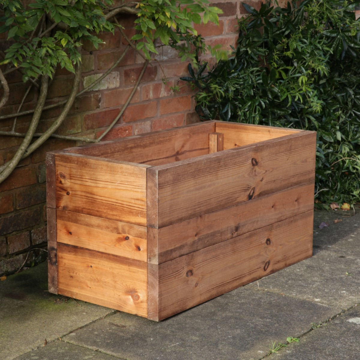 A chunky rectangular wooden planter box on a patio