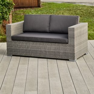A grey rattan outdoor 2 seater sofa with dark grey cushions on a deck