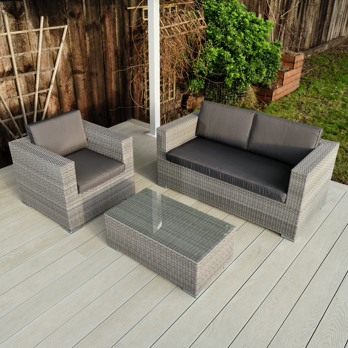 A grey rattan outdoor sofa set with 2 seater sofa, armchair and coffee table on a light grey garden deck