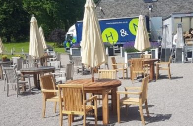 Teak outdoor dining tables chairs and parasols on a gravel terrace with a delivery van unloading in the background