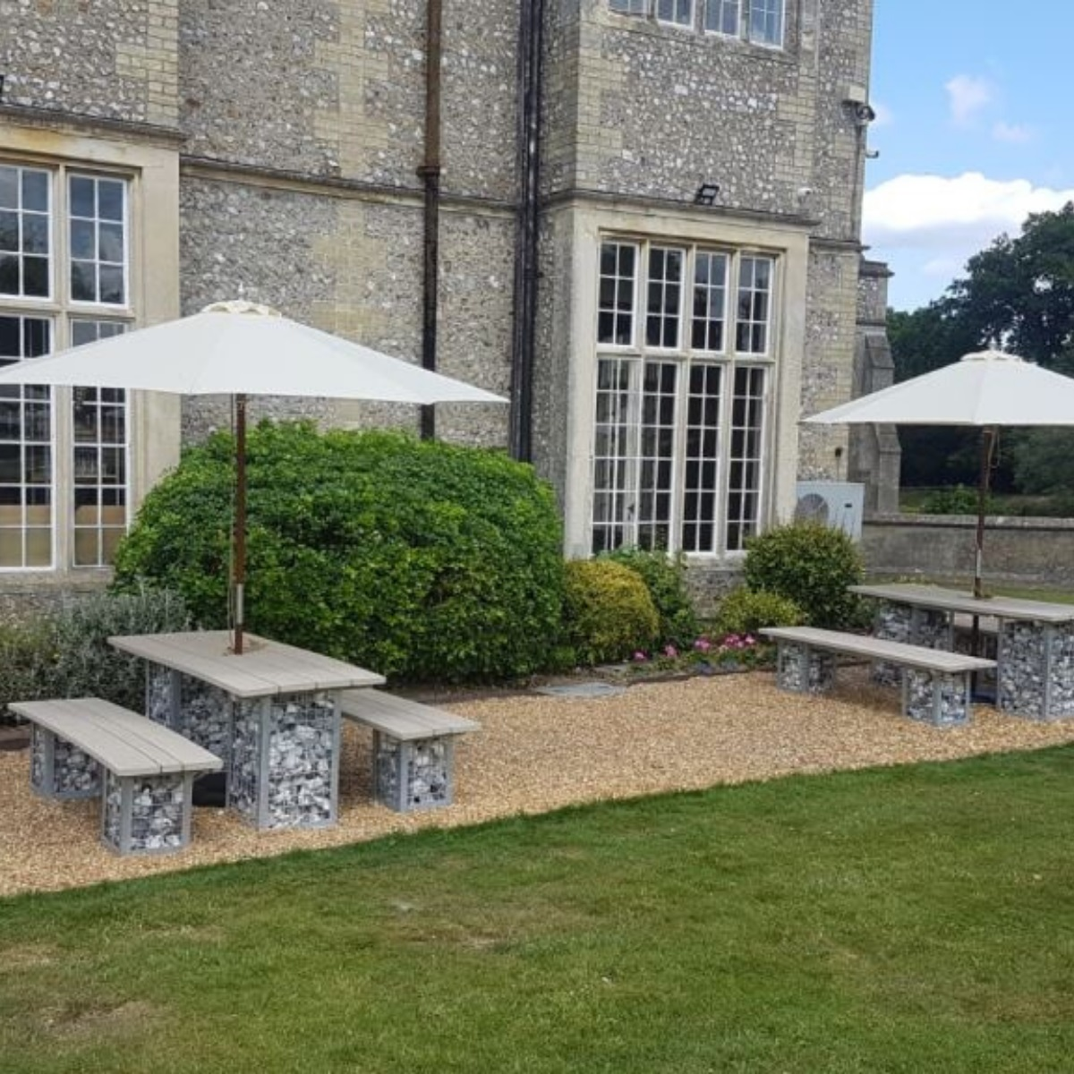 Stone filled gabion legged rectangular tables and benches on the terrace at Devere Horsely Estate Hotel