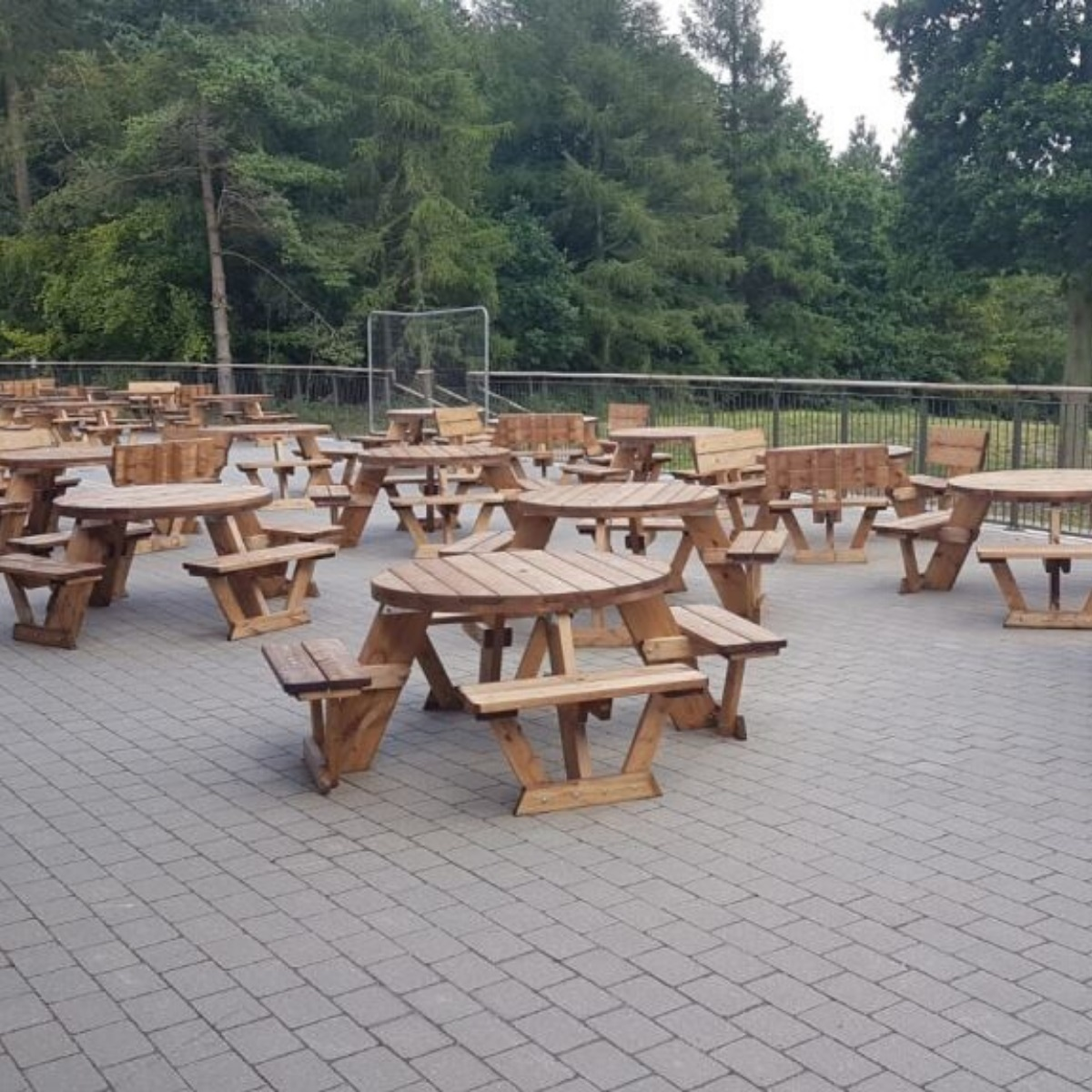 A Patio over looking the Chilterns Forest with a range of wooden 6 and 8 seater round picnic tables on it