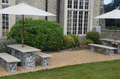 Outdoor rectangular dining tables with wooden tops and stone filled cages as legs situated on gravel at the front of the Horsley Estate Devere Hotel