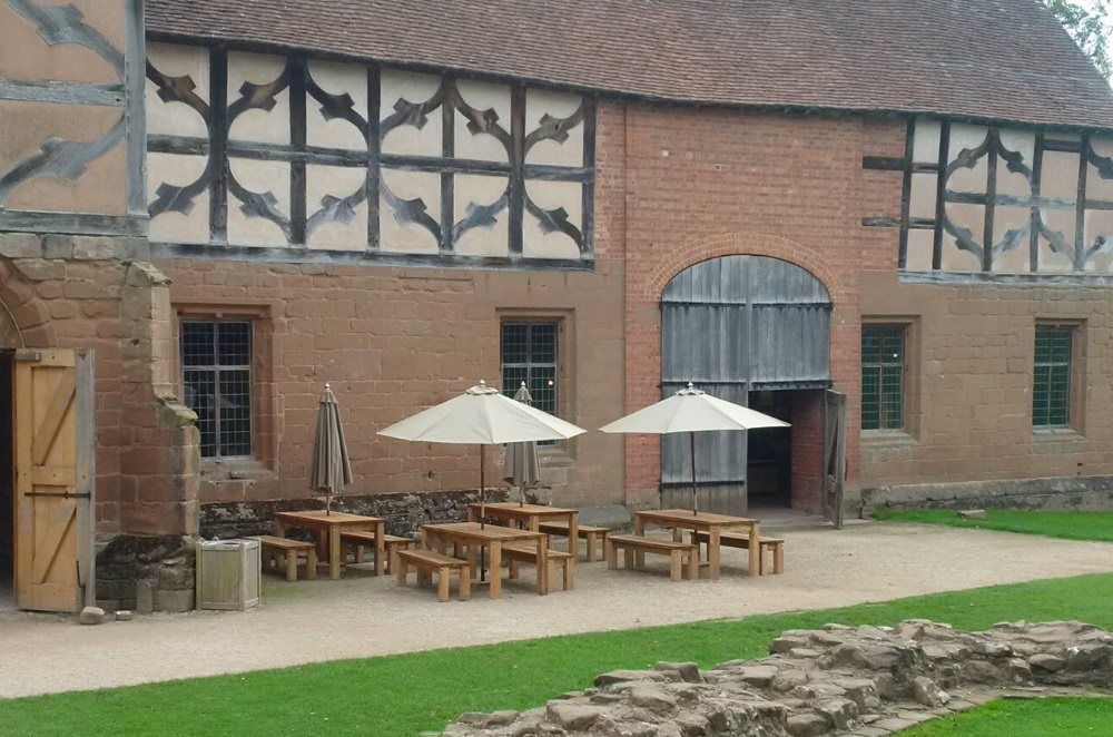 Outdoor wooden rectangular tables and benches at Kenilworth Castle Warwickshire