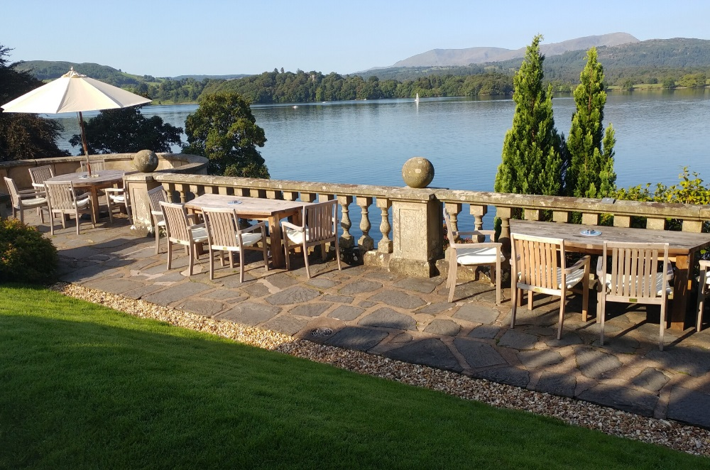 A hotel terrace overlooking a lake in Cumbria with round and half hexagonal wooden outdoor dining tables and teak dining chairs