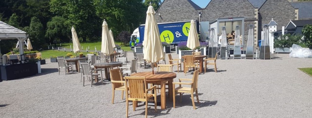 Teak outdoor tables and chairs on a gravel patio at a hotel with a delivey van unloading in the background