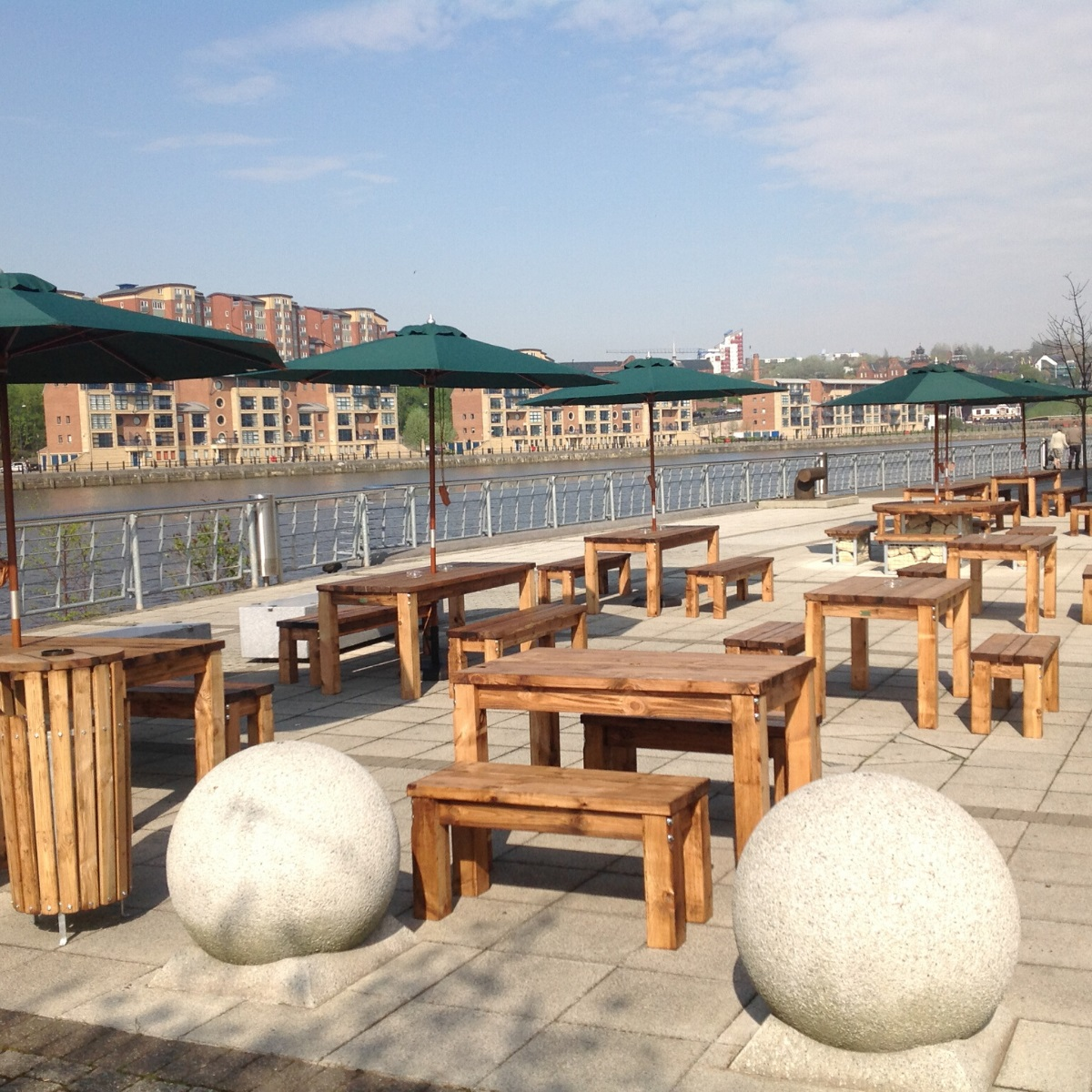 Outdoor wooden rectangular dining tables and benches on a patio at the waters edge of Jurys Inn Hotel Newcastle