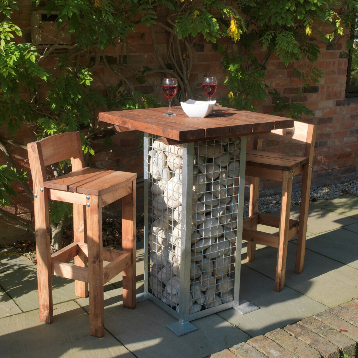 A high poseur table with a wooden top and rock filled metal cage leg with 2 high wooden armchairs on a pub patio