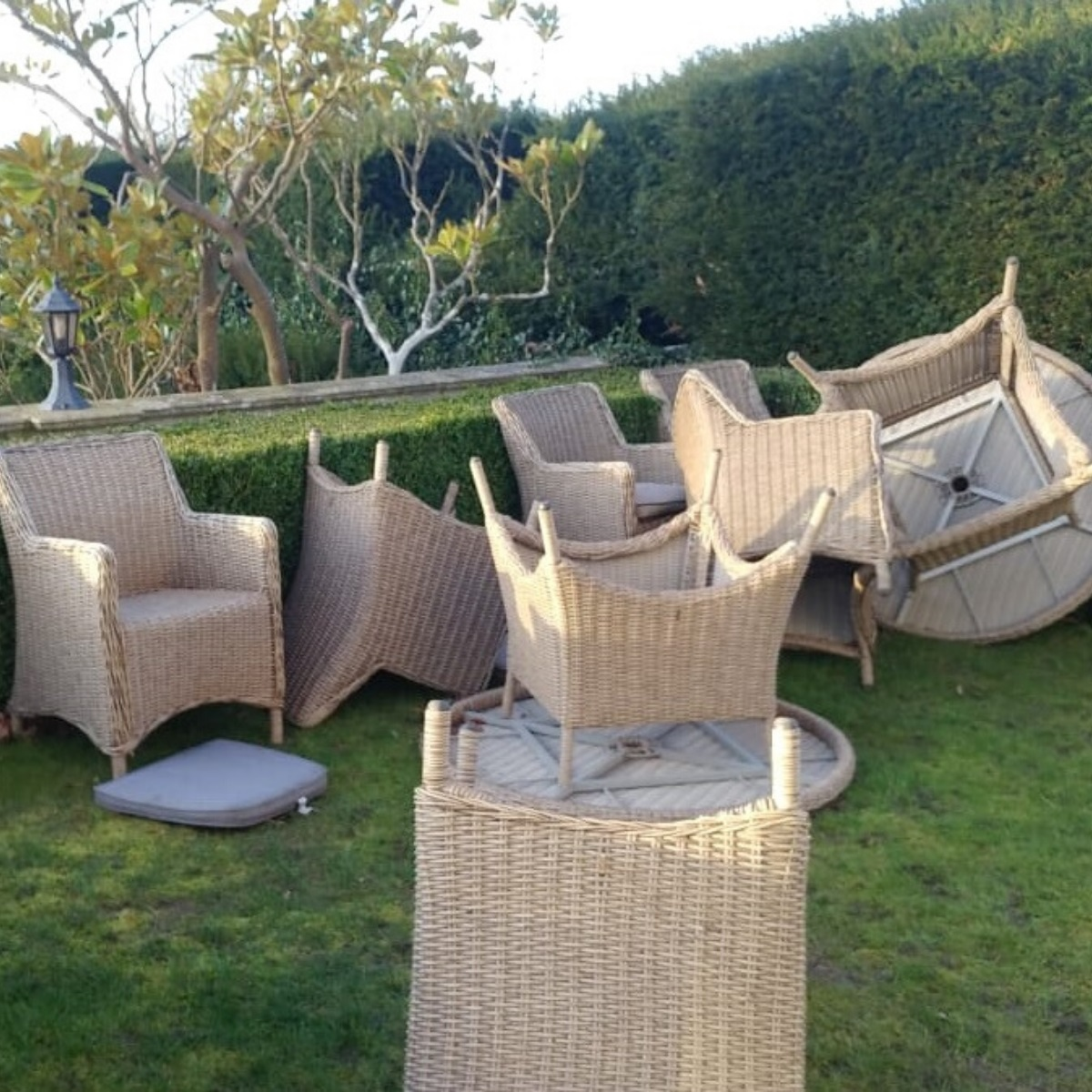 Cream outdoor rattan dining tables and chairs on a hotel lawn blown over by strong winds