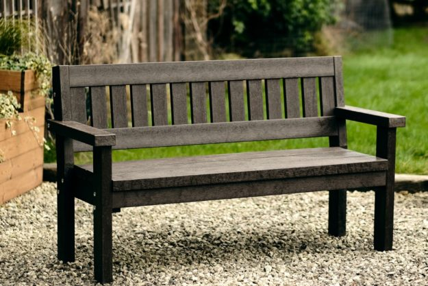 A chunky brown recycled plastic brown bench located on a gravel path