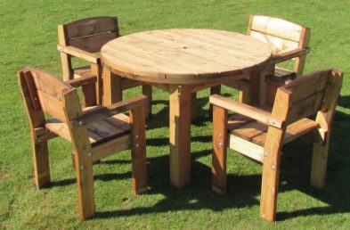A chunky round wooden outdoor table and four pine armchairs around it on a lawn