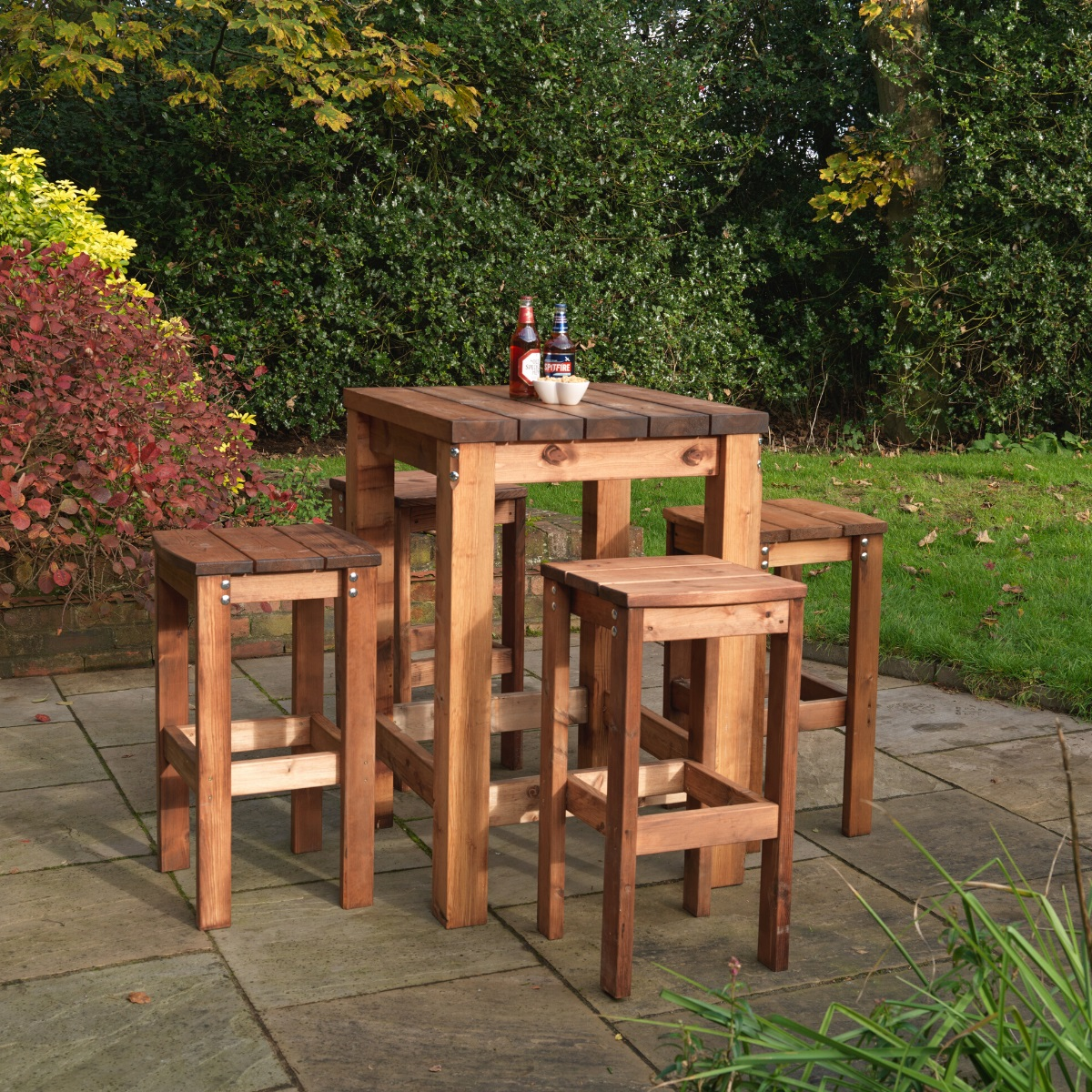 A square wooden poseur table and four bar stools outside on a patio