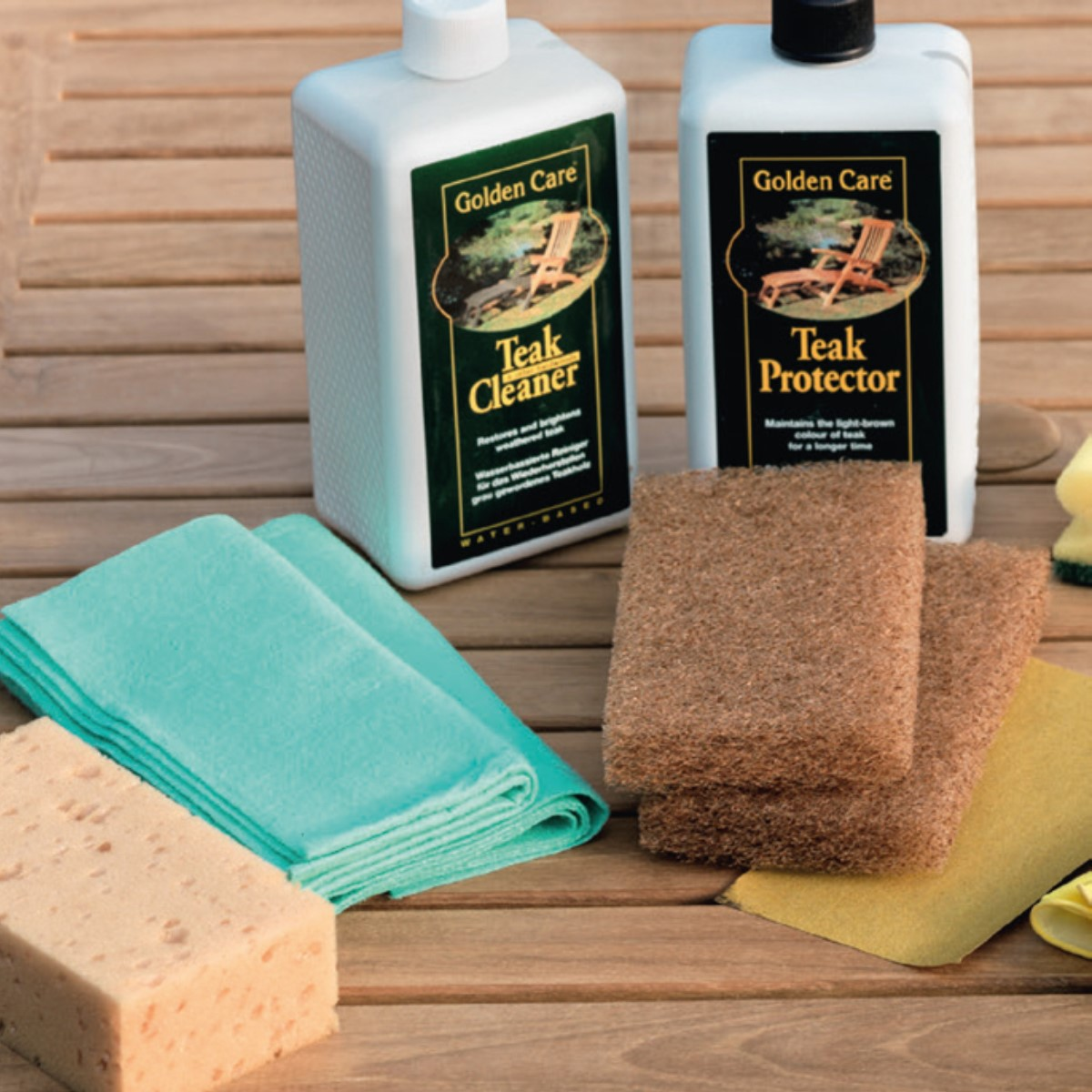 A teak outdoor furniture care kit with treatment fluid bottle and cloths and sponges laid out on a wooden table