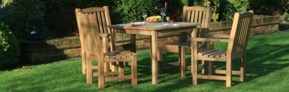 A teak square outdoor dining table and four armchairs on a lawn