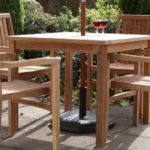 A square teak outdoor dining table and four stacking armchairs around it on a patio