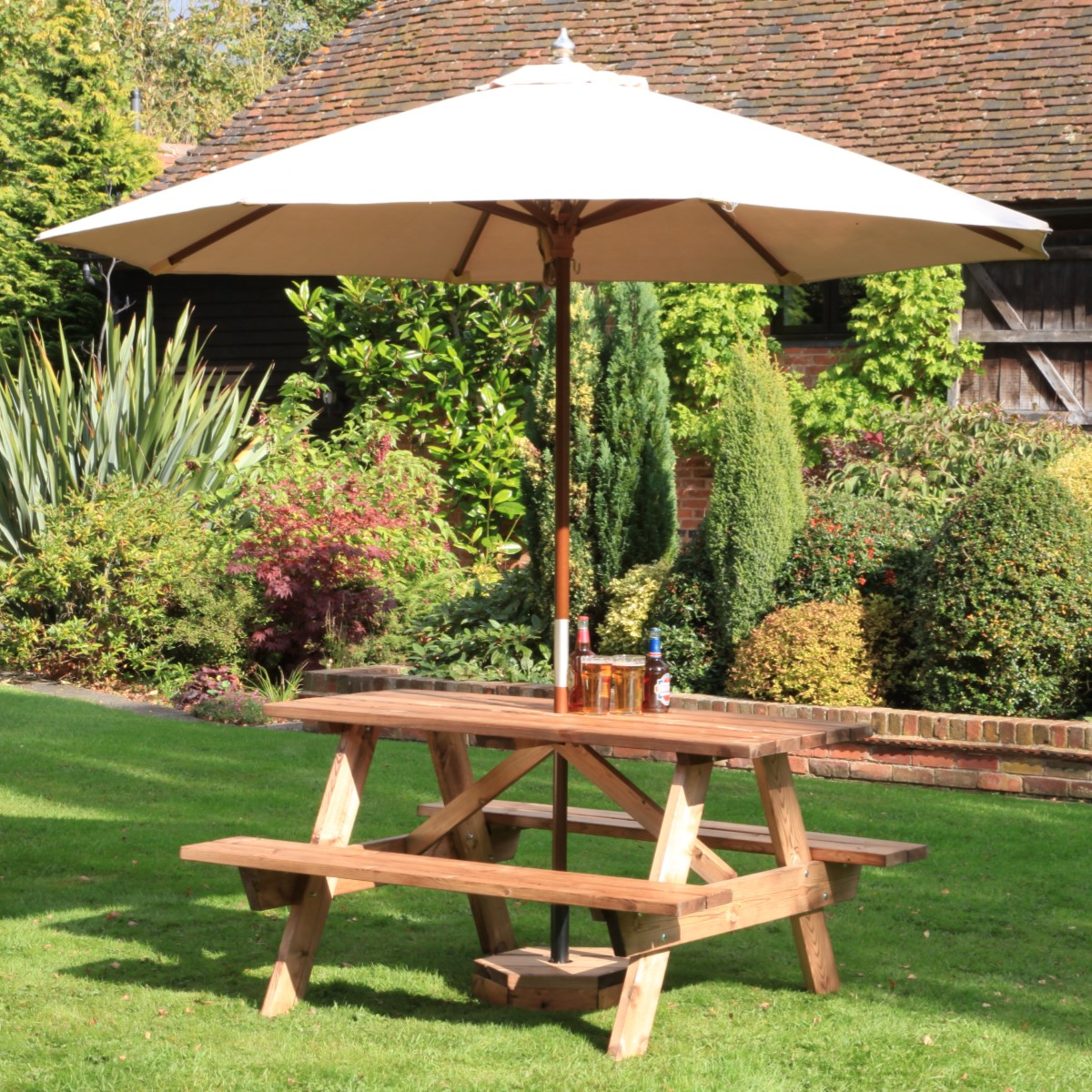 A wooden 6 seater A Frame picnic table on grass with a cream parasol